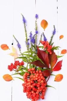 흰색 나무 배경에 열매와 꽃의 가을 장식 위에서 볼