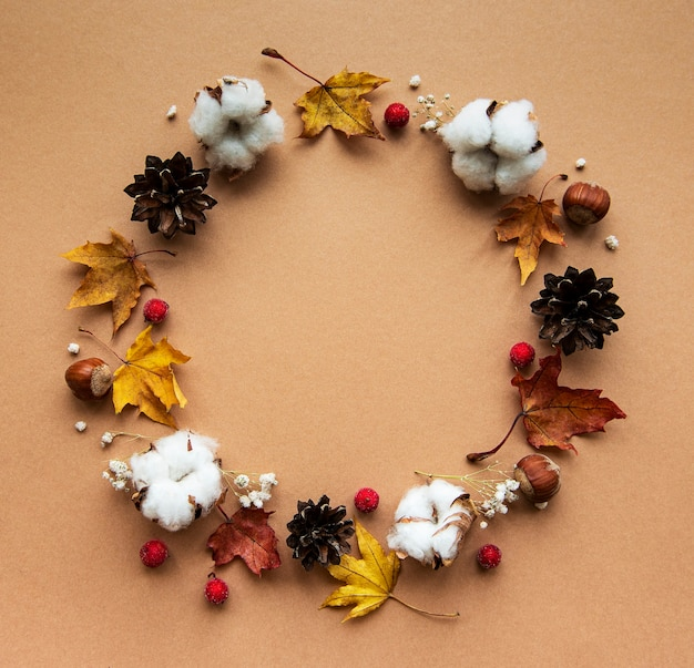 Autumn decoration with cotton flowers and dry maple leaves in the shape of a circle on a brown background