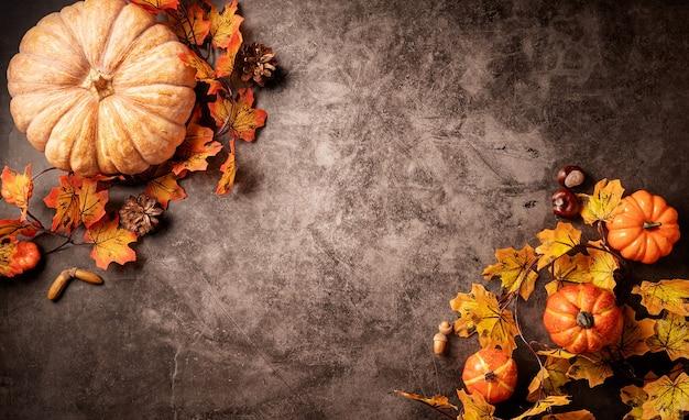 黒の背景にカボチャと葉の秋の装飾
