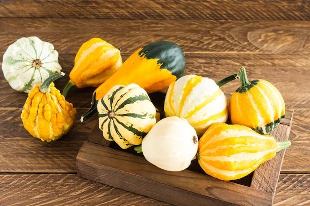 Осенние декоративные тыквы разных форм и цветов в коробке на деревянном фоне.