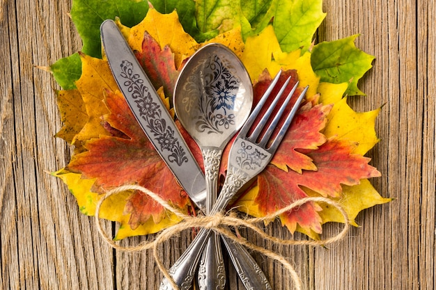 Autumn dinner place setting for thanksgiving holiday with colorful maple leaves on rustic wooden boards