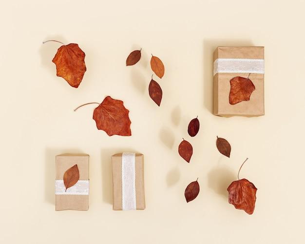 ベージュの赤い乾燥した葉で飾られたクラフト紙からの秋のdiyギフトボックス