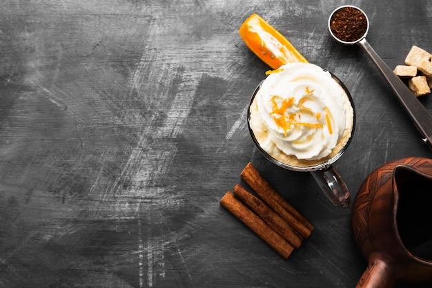 Autumn drink of coffee with orange juice and cream on dark background