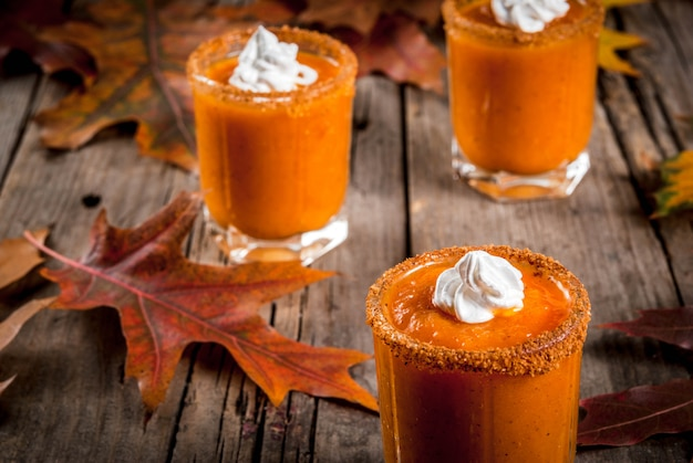 Autumn drink. ideas and recipes for thanksgivings, halloween. alcohol cocktail pumpkin pie vodka shots on old rustic wooden table with fall leaves, copy space
