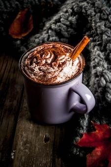 Осенние напитки, горячий шоколад или какао со взбитыми сливками и специями (корица, анис), на старом деревенском деревянном столе, с теплым уютным одеялом, сенной ягодой и листьями copyspace