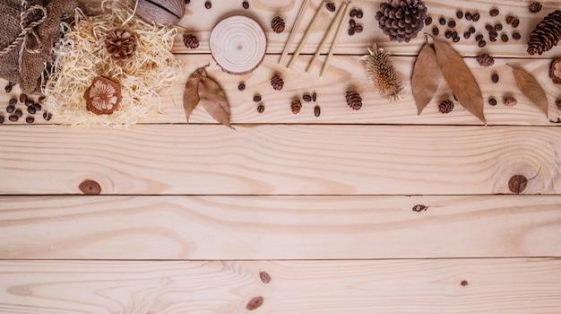 木製の茶色の背景の上面に秋の乾燥葉