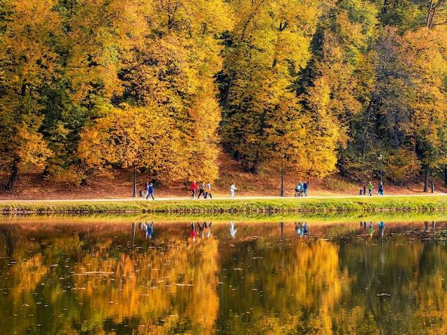 明るい金色の木々、歩く人々、水面の反射がある都市公園の湖沿いの秋の堤防。ツァリツィノ公園、モスクワ。
