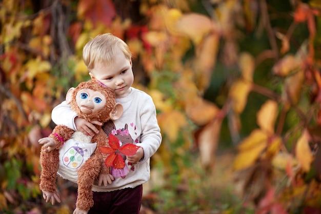 어린 소녀의가 감정적 초상화입니다. 가 공원에서 원숭이 장난감을 가진 예쁜 소녀. 어린이를 위한 가을 활동. 가족을 위한 할로윈과 추수감사절 시간.
