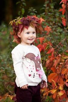 어린 소녀의가 감정적 초상화입니다. 붉은 포도와 예쁜 소녀가 공원에 나뭇잎. 어린이를 위한 가을 활동. 가족을 위한 할로윈과 추수감사절 시간.