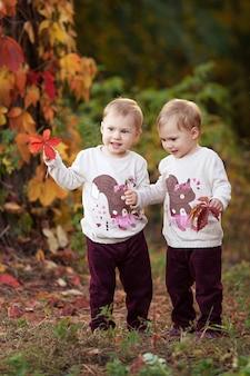 작은 쌍둥이 소녀의 가을 감성적인 초상화. 붉은 포도와 예쁜 소녀가 공원에 나뭇잎. 어린이를 위한 가을 활동. 가족을 위한 할로윈과 추수감사절 시간.
