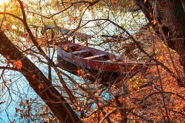 Autumn evening on a deserted river bank with an old fishing bridge and one fishing boat nobody