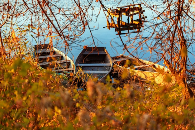 Autumn evening on a deserted river bank with an old fishing bridge and three fishing boats nobody