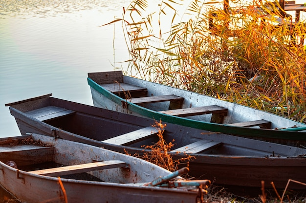 Autumn evening on a deserted river bank with three fishing boats on the bank nobody