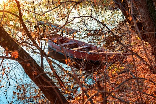 오래된 낚싯대와 낚싯배 한 척이 아무도 없는 황량한 강둑의 가을 저녁