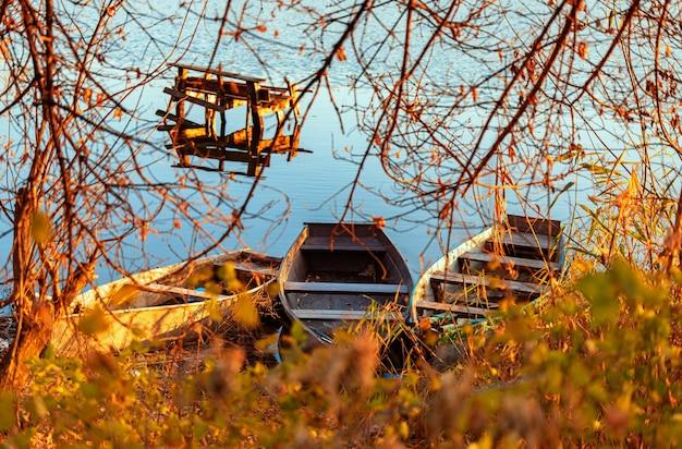 오래된 낚싯대와 3척의 어선이 아무도 없는 황량한 강둑의 가을 저녁