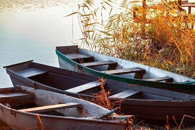 아무도 없는 강둑에 3척의 어선이 있는 황량한 강둑의 가을 저녁