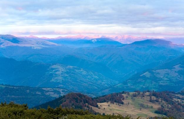 山の欲望の黄金色のピンクの日光と空の夜の輝きと秋の夜の高原の風景