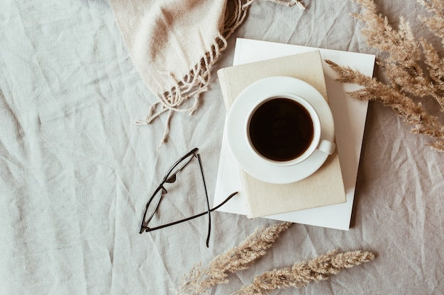 Autumn, fall composition. a cup of coffee lying on the grey linen bed with beige warm blanket, books, glasses and reeds