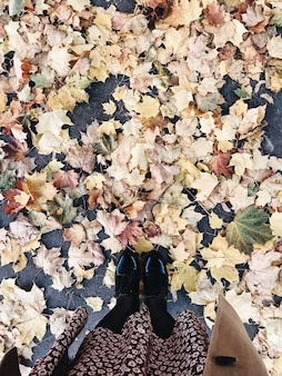 Autumn and fall composition. woman in black boots, cute skirt and beige coat standing on dried foliage