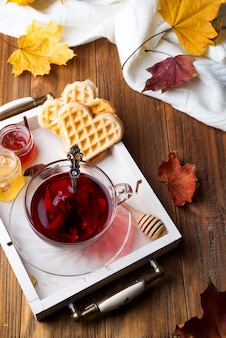 Autumn fall concept with knitted blanket and hot tea with waffer, jam, honey