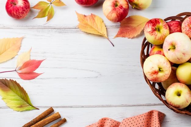 Осенью плоско лежат композиции со спелыми красными яблоками, желтыми листьями, корицей.