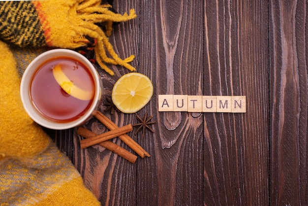 秋秋フラットレイトップビュー秋は碑文の木製の背景とお茶のマグカップを残します