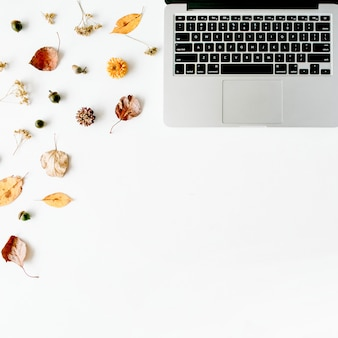 秋秋フラットレイ、トップビューホームオフィスデスク。ノートパソコン、どんぐり、白地に黄色の葉のあるワークスペース
