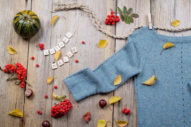 Осень осень плоская планировка, вид сверху. теплый вязаный свитер, осенние листья, каштаны, рябина и тыква с надписью «осень привет, на деревенском деревянном фоне