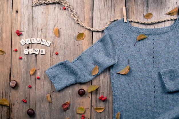 Осень осень плоская планировка, вид сверху. теплый вязаный свитер, осенние листья, каштаны, рябина и тыква с надписью «осенняя пора» на деревенском деревянном фоне
