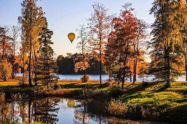 Осенний осенний пейзаж с прудом, озером и воздушным шаром