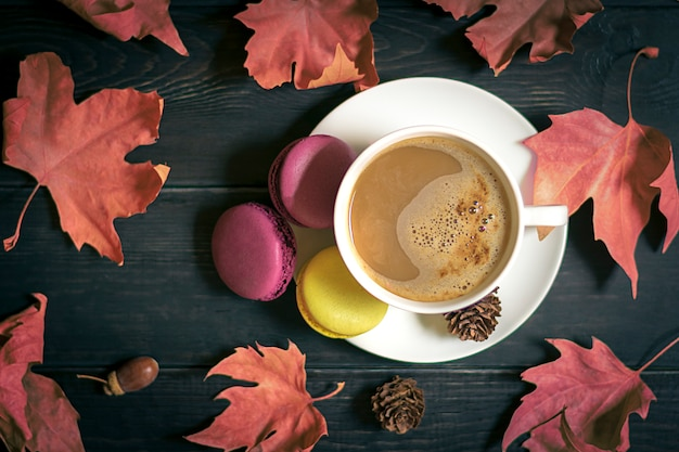 Autumn, fall leaf, hot steaming cup of cappuccino coffee, macaroon, cone on wooden table b