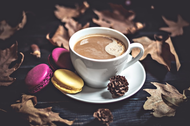 Autumn, fall leaves, hot steaming cup, cappuccino coffee, macaroon, cone on wooden table b
