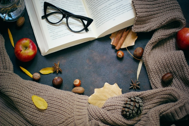 Autumn, fall leaves, hot steaming cup of coffee and a warm scarf or cardigan. seasonal, morning coffee, sunday relaxing and still life concept.
