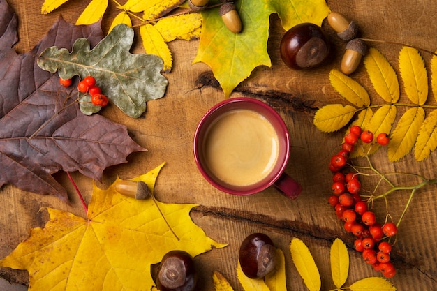 Autumn, fall leaves, hot steaming cup of coffee on wooden table  sunday morning coffee relaxing and still life concept. top view.