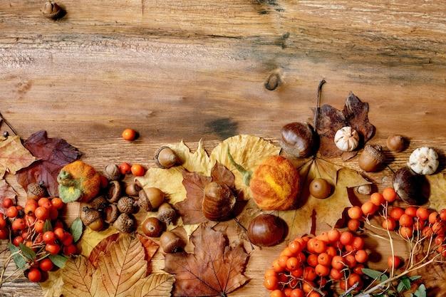黄色のカエデの葉、ナナカマドの果実、栗、木製のテクスチャ背景に装飾的なカボチャと秋の秋の季節の組成物。フラットレイアウト、コピースペース