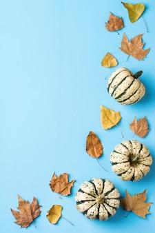 가을 추수 감사절에는 장식용 오렌지 호박과 말린 잎이 있습니다. 평면도, 평면도, 복사 공간, 인사말 카드의 정물 배경