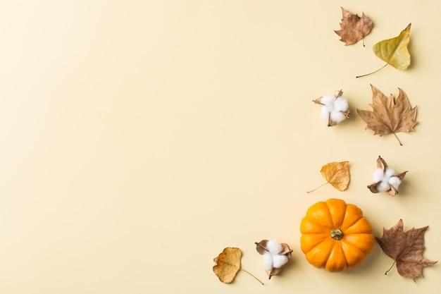 가을 추수 감사절에는 장식용 오렌지 호박과 말린 잎이 있습니다. 평면 위치, 위쪽 보기, 복사 공간, 인사말 카드의 정물 노란색 배경