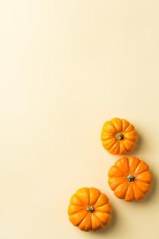 Осенний осенний состав на день благодарения с декоративными оранжевыми тыквами. плоская планировка, вид сверху, копия пространства, натюрморт желтый фон для поздравительной открытки