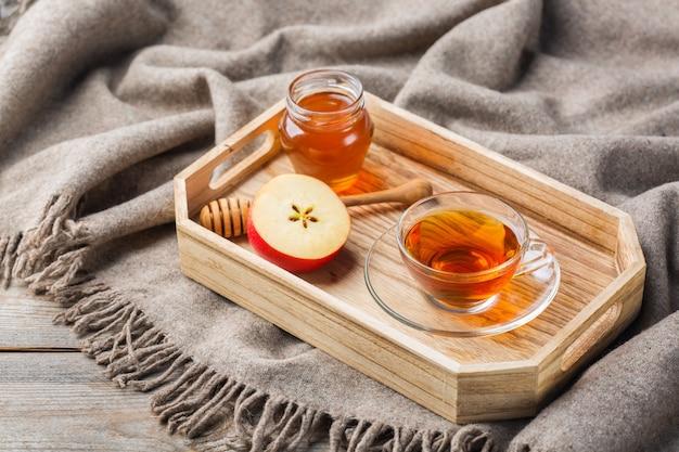 飲み物とヒュッゲスタイルの秋、秋、冬の家の装飾。はちみつ入りの温かいお茶、温かみのあるウールのスカーフ、素朴な木製のテーブルに柔らかいチェック柄の季節の組成物。