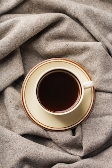 スカンジナビア、ヒュッゲスタイルの秋、秋、冬の家の装飾。一杯のコーヒー、暖かいウールのスカーフ、素朴な木製のテーブルの上に柔らかい格子縞の季節の構成。
