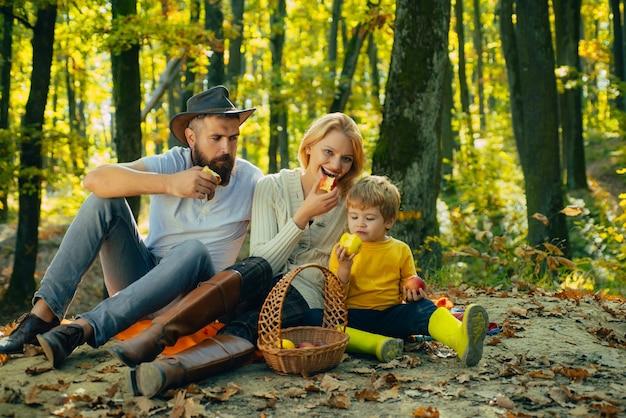 公園でキャンプし、リンゴのアクティブな人々と幸せな家族のコンセプトを屋外で食べる秋の家族...