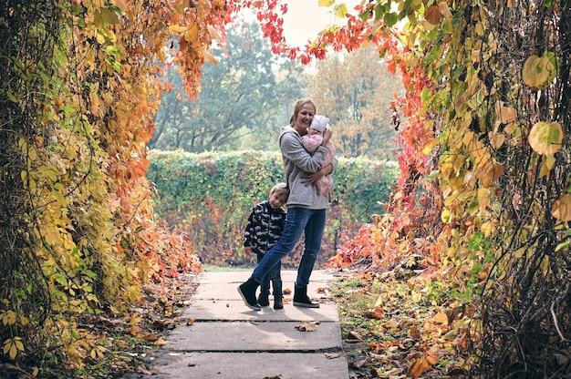 Осенняя семейная прогулка в лесу. красивый парк с сухими желтыми и красными листьями. любящая мать обнимает дочь и сына.