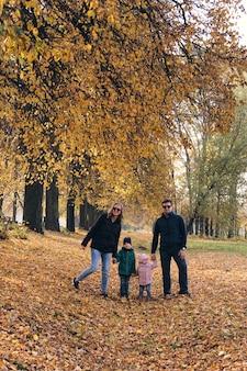 Осенняя семейная прогулка в лесу. красивый парк с сухими желтыми и красными листьями. мать с дочерью и отцом с сыном и отцом, взявшись за руки.