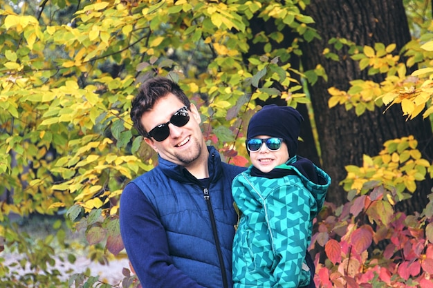 Осенняя семейная прогулка в лесу. красивый парк с сухими желтыми листьями. сын и отец, держась за руки.