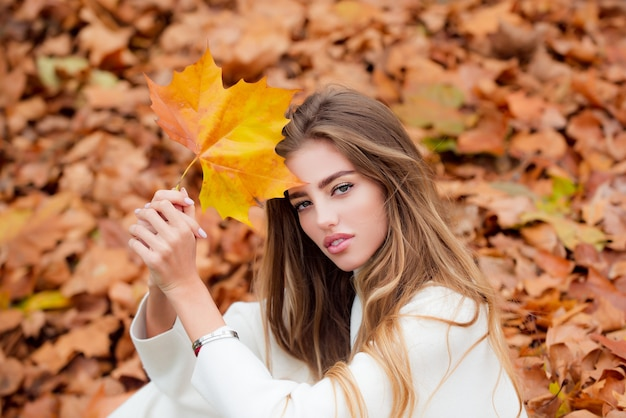 Autumn fashion concept stylish girl in autumnal style posing on red maple leaf background outdoors