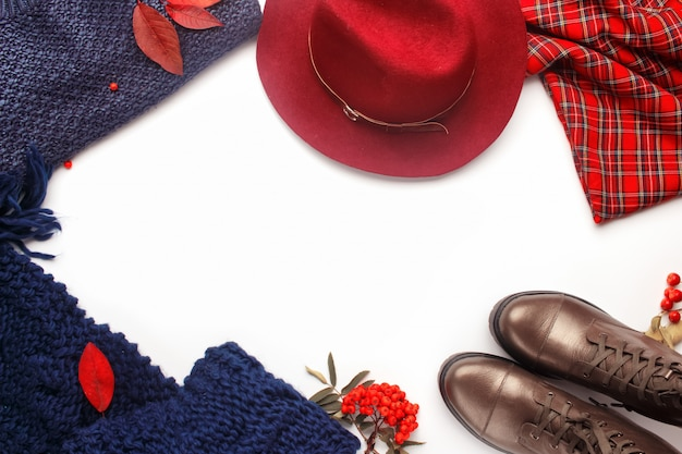 Autumn fashion frame composition. flat lay with stylish feminine autumn clothes and accessories: boots, burgundy hat, a cozy knitted scarf, warm sweater and tartan skirt.
