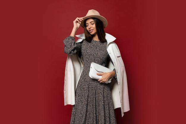 秋のファッションルック。トレンディな白いジャケットとプリントポーズのドレスでゴージャスなヨーロッパのブルネットの女の子。革製のハンドバッグを持っています。