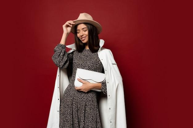 가을 패션 룩. 유행 흰색 재킷과 인쇄 포즈와 드레스에 화려한 유럽 갈색 머리 여자. 가죽 핸드백을 들고.