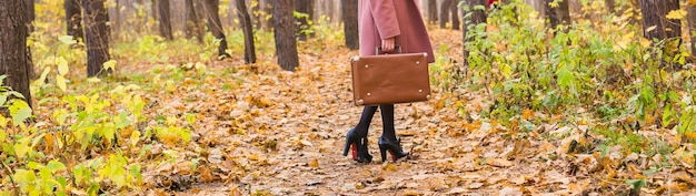 Autumn, fashion, people concept - close up of woman with brown retro suitcase walking through the autumn park