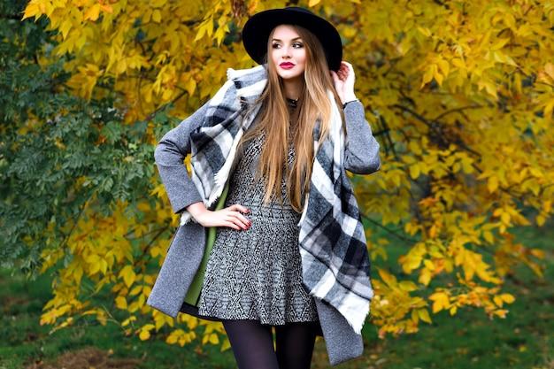 素晴らしい都市公園、スタイリッシュなコート、バックパック、ヴィンテージの帽子でポーズをとるエレガントな魅力的な女性の秋のファッションの肖像画。一人歩き、寒い